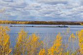 stock photo of barge  - Photo of autumn landscape with barge on river Volga - JPG