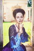 image of dress-making  - Beautiful medieval woman in blue dress making silence gesture outdoor - JPG