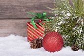 foto of pine-needle  - Red Christmas ball with pine needles and cone on snow on a wooden background - JPG