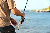 foto of rod  - Modern clean fishing rod in hands ourdoors  - JPG