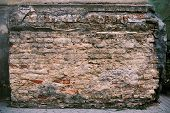 stock photo of pilaster  - fragment of brick pilaster with crumbling plaster - JPG