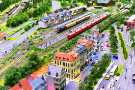 picture of passenger train  - view of toy hobby railroad layout with railway station building passenger and freight cargo trains on rail tracks  - JPG