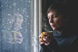 image of heartbreaking  - Lonelsome woman drinking cup of coffee by the window of her living room while the snow is falling outside - JPG