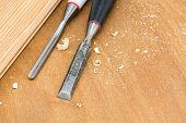 stock photo of chisel  - Carpenter chisel tool with shavings on wooden background - JPG