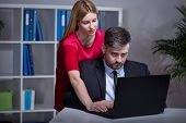 stock photo of inappropriate  - Beautiful female boss helping her older handsome employee - JPG