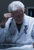 picture of radiogram  - Physician sitting at the desk and reading x - JPG