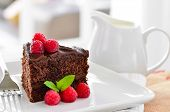 picture of chocolate fudge  - Fresh Home Made Sticky Chocolate Fudge Cake With Raspberries and a jug of fresh pouring cream - JPG