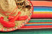stock photo of mexican fiesta  - fiesta mexican poncho rug in bright colors with sombrero background with copy space - JPG