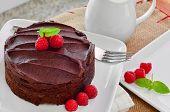 stock photo of chocolate fudge  - Fresh Home Made Sticky Chocolate Fudge Cake With Raspberries - JPG