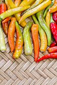 stock photo of yellow-pepper  - pile of yellow and red thai goat pepper on bamboo plate - JPG