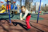 stock photo of seesaw  - Cute little girl swinging on seesaw on children playground - JPG
