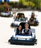 picture of amusement park rides  - girls on go cart with a motion blur background - JPG
