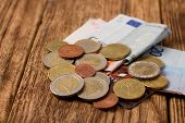 picture of significant  - Horizontal photo of euro Coins bills and credit card on one heap placed on old worn wooden board with significant grooves - JPG