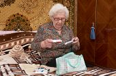 foto of prescription  - Senior caucasian woman in glasses about ninety years old sits on the sofa takes out pills from the sack and reads prescriptions in her bed room - JPG
