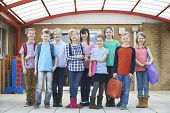 stock photo of pupils  - Portrait Of School Pupils Outside Classroom Carrying Bags
