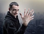 stock photo of ape-man  - Surprised man looks at his strange hand - JPG