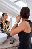 picture of early morning  - young professional business women with jewellery earings watch early morning at home bathroom - JPG