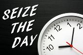 picture of time flies  - The phrase Seize The Day in white text on a blackboard next to a modern wall clock displaying the time - JPG