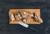 picture of baguette  - French baguette cut into pieces on a rustic wooden board with knife over dark old painted background - JPG