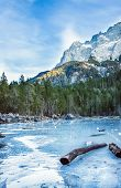 picture of bavarian alps  - Frozen forest lake in Bavarian Alps near Eibsee lake in winter with mountains at the backdrop - JPG