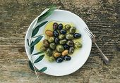 picture of olive branch  - A plate of Mediterranean olives in olive oil with a branch of olive tree and a small silver fork over a rough old wooden desk - JPG