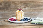 stock photo of maple syrup  - Pancakes with creamy cheese topping garden berries and maple syrup over a rustic wooden background - JPG