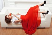 stock photo of yoke  - Girl in red dress lying on a white sofa - JPG