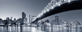 stock photo of bridge  - Queensboro Bridge over New York City East River black and white at night with river reflections and midtown Manhattan skyline illuminated - JPG