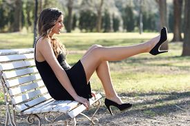 stock photo of sitting a bench  - Portrait of funny woman model of fashion with very long legs sitting on a bench in an urban park wearing black dress and high heels - JPG