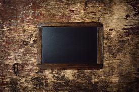 stock photo of decomposition  - Small wooden framed blank chalkboard on a old dark background - JPG