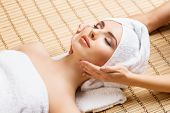 Beautiful, young and healthy woman on bamboo mat in spa salon having face massage. Spa, health and h poster