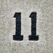 Number 11 painted black house number address sign on painted white stone wall textured background poster