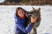 Portrait Of A Girl Trainer And A Gray Wolf In A Snowy Field poster