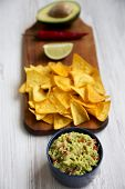 Bowl Of Traditional Mexican Guacamole With Nachos On Rustic Wooden Board, Low Angle View. poster