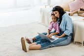 Pretty African American Woman With Adorable Daughter Using Laptop While Sitting On Carpet Near Sofa poster