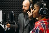 Male and female singers in audio recording studio poster