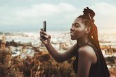 An Excited Young African Female With Braids Is Smiling And Photographing Cityscape From The Mountain poster