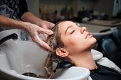 Beautiful Young Woman Sitting Near Sink While Hairdresser Washing Her Hair In Beauty Salon. Hair Sty poster