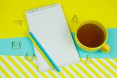 Top View Notebook With Blank White Paper Sheet, Pencilsand Cup Of Tea On A Blue And Yellow Trendy Vi poster