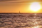 Single Yacht On The Ocean Waves With Large Bright Sun On Right And Orange Sky, Ocean Has Small Waves poster