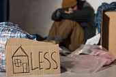 Selective Focus Of Homeless Man Holding Head On Knees While Sitting On Rubbish Dump With Cardboard C poster