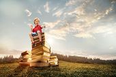 Little Boy Sitting On The Tower Made Of Big Books. Childhood Dreams, Reading And Education Concept.  poster