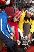 image of ski boots  - Family Trying On Ski Boots In Hire Shop - JPG