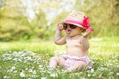 Baby Girl In Summer Dress Sitting In Field Wearing Sunglasses And Straw Hat