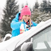 stock photo of ice-scraper  - Woman cleaning car windshield of snow winter happy young scraper - JPG