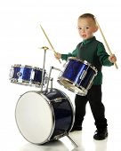 An adorable preschooler with drum sticks poised, waiting for a signal to begin his drum routine.  On