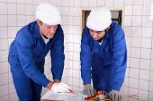 Experienced tradesman teaching his apprentice how to read a blueprint