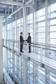 Full length of businessmen shaking hands by railing in modern office