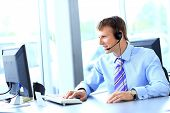 picture of telemarketing  - Happy young man working at callcenter - JPG