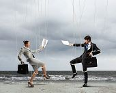 stock photo of obey  - Image of businesspeople hanging on strings like marionettes against sea background - JPG